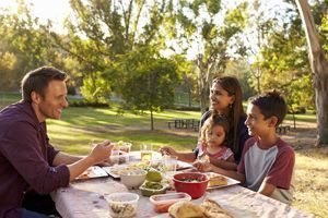 Mixed race family enjoying a picnic at a table in a park