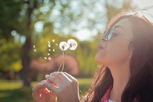 Beautiful young woman blowing dandelion