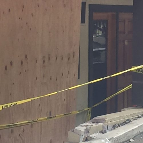 Plywood and caution tape covering the room involved in the crash
