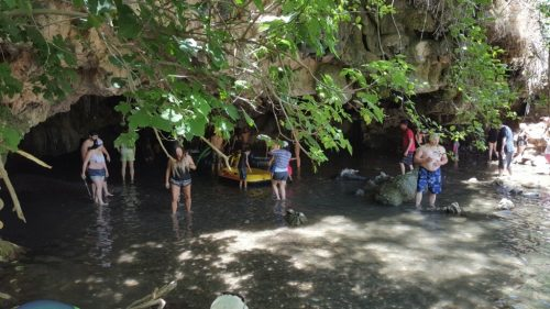 Natural Bridges visitors wading under an arch
